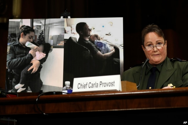 U.S. Border Patrol Chief Carla Provost testifies by a photo of agents taking care of children during a Senate Judiciary border security and immigration subcommittee hearing about the border, May 8, 2019.