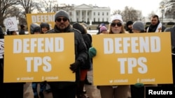 Demonstrators hold signs protesting the termination of Salvadorans' Temporary Protected Status