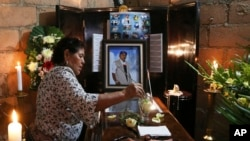 A woman dips a flower in a glass of water placed on the coffin of slain journalist Gumaro Perez during his wake in Acayucan, Veracruz state, Mexico, Dec. 20, 2017.