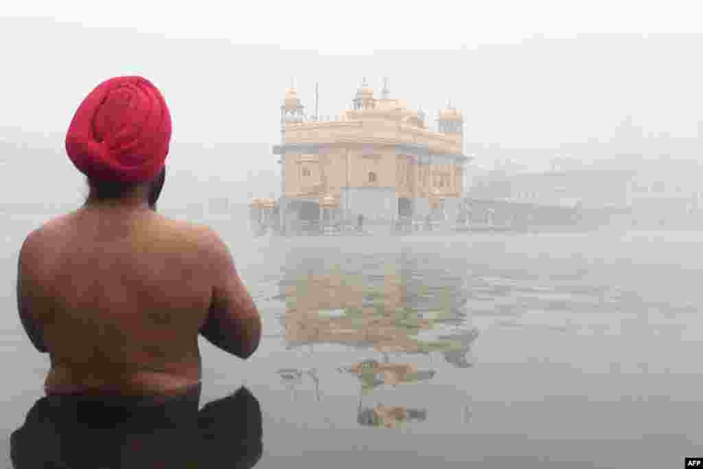 A devotee prays at the Sikh shrine the Golden Temple amid dense fog conditions in Amritsar, India.