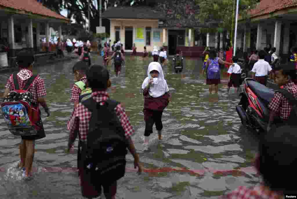 طلبہ و طالبات سیلابی پانی سے گزر رہے ہیں۔