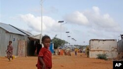 A Somali child stands under the solar powered lights at a refugee camp that were installed to help combat the rampant rapes that were occurring at night, in Mogadishu, Somalia, July 17, 2013.