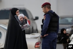 A Bahraini protester holds up a picture of Saudi Shi'ite cleric Sheikh Nimr al-Nimr in front of a riot police officer in Daih, a largely Shi'ite suburb of the capital, Jan. 4, 2016.