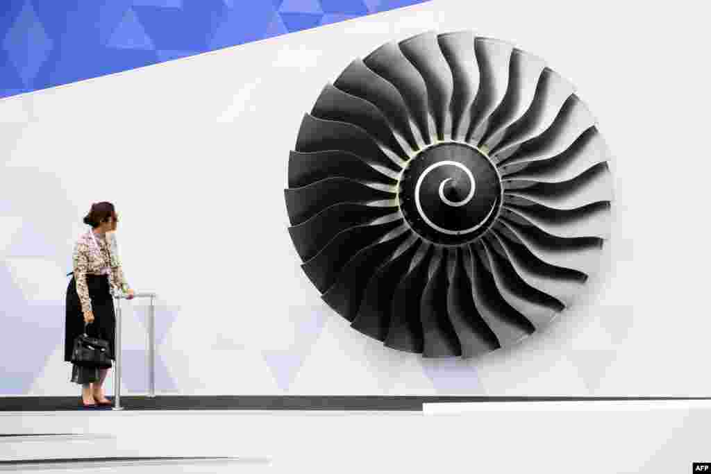 A woman stands near a model of a Rolls Royce Trent engine at the Farnborough Air Show in Hampshire, southern England.