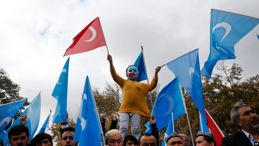 FILE - A child from the Uighur community living in Turkey, who is wearing a mask in the colors of the flag which ethnic Uighurs call East Turkestan and with a painted hand with the colors of China's flag, participates in a protest in Istanbul, Nov. 6, 2018.