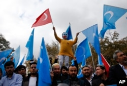 FILE - A child from the Uighur community living in Turkey, who is wearing a mask in the colors of the flag which ethnic Uighurs call East Turkestan and with a painted hand with the colors of China's flag, participates in a protest in Istanbul, Nov. 6, 2018, against alleged oppression by the Chinese government to Muslim Uighurs in the far-western Xinjiang province.