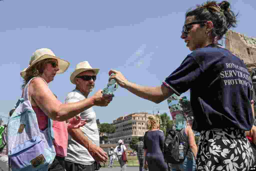 پخش بطری های آب از سوی اعضای حفاطت مدنی ایتالیا به گردشگران در مرکز رم