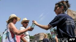 Members of the Italian Civil Protection (Protezione Civile) give water bottles to people and tourists in front of the Ancient Colosseum in central Rome. Italy experienced a heatwave in August 2018. (AFP PHOTO / Andreas SOLARO)