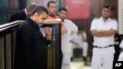 Canadian Al-Jazeera English journalist Mohammed Fahmy, left, listens during his retrial in a courtroom, in Tora prison, in Cairo, Egypt, June 25, 2015.