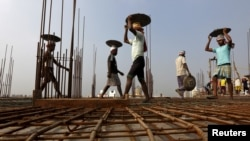 FILE - Laborers work at the construction site of a residential complex on the outskirts of Kolkata, India.