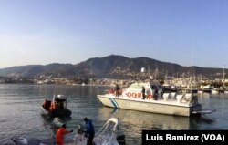 """Protesters at Mytilini harbor on Lesbos hold a banner between two boats that reads """"Ferries Are for Safe Passage, Not for Deportation,"""" as a Greek coast guard vessel approached and its crew ordered the protesters to move, April 4, 2016."""