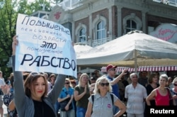 "FILE - People attend a rally against planned retirement age hikes, in Krasnodar, Russia, Sept. 9, 2018. The poster at left reads: ""Pension age hike amounts to lifetime slavery."""