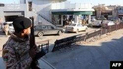 Un soldat de l'armée libyenne monte la garde devant une station-service dans la capitale Tripoli le 14 décembre 2013.