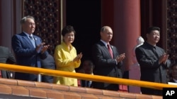ប្រធានាធិបតីចិនលោក Xi Jinping (ខាងស្តាំ) ទះដៃជាមួយប្រធានាធិបតីកាហ្សាស្តង់ Nursultan Nazarbayev (ខាងឆ្វេង) ប្រធានាធិបតីកូរ៉េខាងត្បូងលោកស្រី Park Geun-hye និងប្រធានាធិបតីរុស្ស៊ីលោក Vladmir Putin នៅអំឡុងពេលដង្ហែក្បួនយោធានៅក្រុងប៉េកាំង នាថ្ងៃទី០៣ ខែកញ្ញា ឆ្នាំ២០១៥។