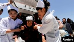 Nurses support an injured woman who is taken to a hospital in Minxian county, Dingxi, Gansu province, July 22, 2013.