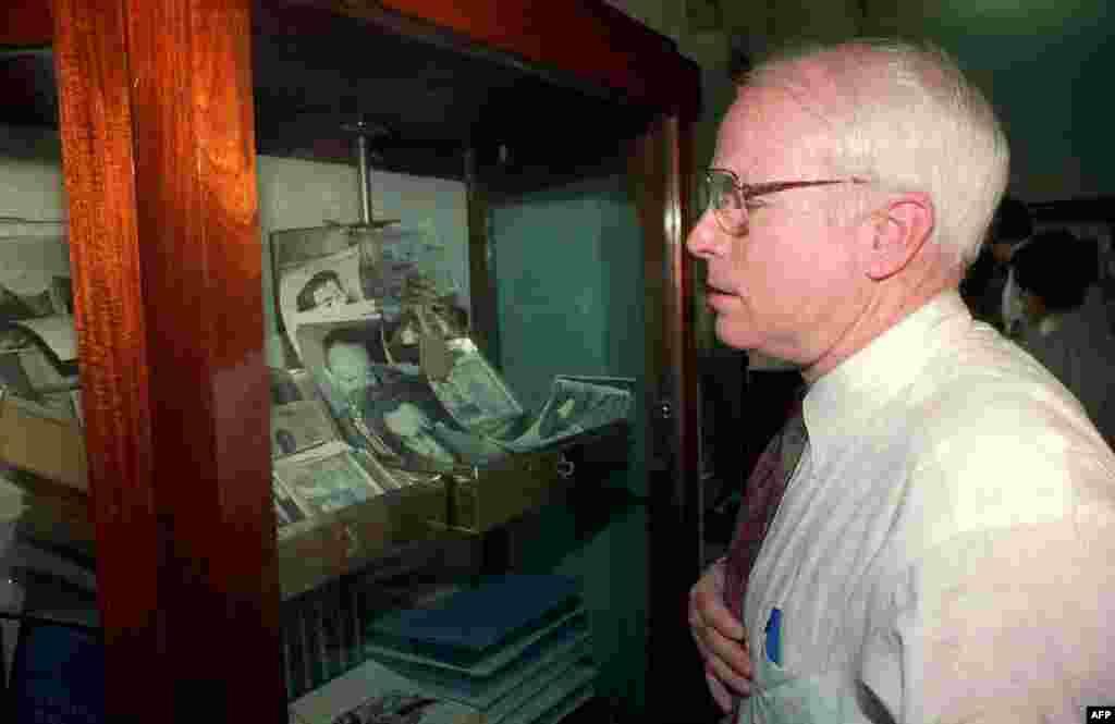 Thượng nghị sĩ Hoa Kỳ John McCain ngắm nhìn những hiện vật là tư trang của các tù binh chiến tranh Mỹ tại trung tâm lưu trữ về tù binh chiến tranh/quân nhân mất tích trong chiến sự tại Bảo tàng Lịch sử Quân sự ở Hà Nội, ngày 31 tháng 5 năm 1993. Ông đi cùng Thượng nghị sĩ Hoa Kỳ John Kerry, người cũng là một cựu quân nhân chiến tranh Việt Nam và sau này trở thành bộ trưởng ngoại giao Mỹ, và một phái đoàn trong một chuyến thăm kéo dài hai ngày nhằm vận động Việt Nam cho phép họ tiếp cận thêm các kho lưu trữ chứa thông tin về số phận của các quân nhân Mỹ mất tích.