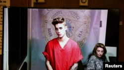 Getting arrested for driving drunk and drag racing on a main thoroughfare in a rented sports car is a bit of fiasco. Pop singer Justin Bieber might have a different word for it. Here, he appears via video conference in his first court appearance in Miami, Florida, January 2014. (REUTERS FILE PHOTO)