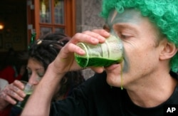 Contestants drink green beer at the first stage of the annual 3 legged race, on St Patrick's Day in Copenhagen, Denmark, Thursday March 17, 2005.