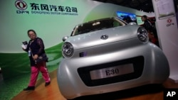 A visitor looks at an E30 EV, a small electric vehicle of Chinese state-owned automobile manufacturer Dongfeng Motor Co., at China International Industry Fair in Shanghai, Nov. 5, 2013.
