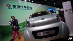 FILE - A visitor looks at an E30 EV, a small electric vehicle of Chinese state-owned automobile manufacturer Dongfeng Motor Co., at China International Industry Fair in Shanghai, Nov. 5, 2013.