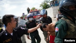 FILE - Security forces detain a man during clashes with garment workers in Phnom Penh, Cambodia, Nov. 12, 2013.
