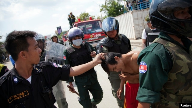 Security forces detain a man during clashes with garment workers in Phnom Penh, Cambodia, Nov. 12, 2013.