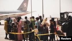 在阿富汗首都喀布爾的哈米德·卡爾扎伊國際機場,平民準備登機。 (2021年8月18日)