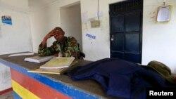 2014年7月6日,一名警察坐在襲擊現場附近。肯尼亞沿海的甘巴地區的警察局遇襲,他的同事被打死