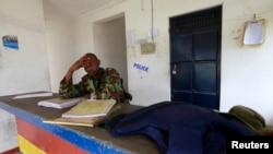 2014年7月6日,一名警察坐在袭击现场附近。肯尼亚沿海的甘巴地区的警察局遇袭,他的同事被打死