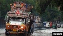 پشاور میں بارش کے بعد ایک بس پانی میں ڈوبی ہوئی سڑک سے گزر رہی ہے۔ فائل فوٹو