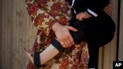 파키스탄 페샤와르 시에서 13살 소아마비 환자가 가족의 품에 안겨있다. (자료사진)