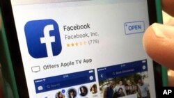 FILE - In this June 19, 2017, file photo, a user gets ready to launch Facebook, in North Andover, Massachusetts.
