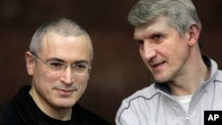 Mikhail Khodorkovsky, left, and his co-defendant Platon Lebedev talk behind a glass enclosure at a court room in Moscow, Russia, Dec. 30, 2010.