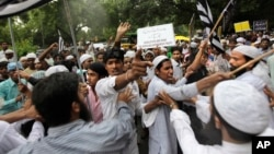 FILE - Indian Muslim men shout slogans during a protest against tensions in India's northeastern state of Assam, in New Delhi, India, Aug. 8, 2012.