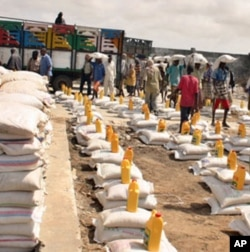 Relief workers prepare to distribute food-aid rations at a camp for the internally displaced in Mogadishu.