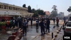 Des pompiers s'activent à éteindre le feu sur trois véhicules endommagés et partiellement incendiés à l'explosion d'une grenade près de la Banque commerciale Kenya à Bujumbura, Burundi vendredi 29 mai 2015. (Edward Rwena - VOA