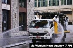 Nhân viên của quân đội phun thuốc khử trùng trên đường phố ở Hà Nội, ngày 7 tháng 3, 2020.