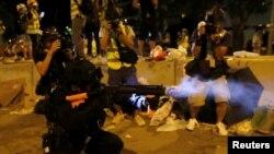 在香港抗议者冲入立法会后,一名香港警察在立法会外向示威者发射催泪弹。(2019年7月1日)