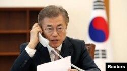Nouvo Prezidan Sid Koreyen an, Moon Jae-in, nan moman li tap pale nan telefòn ak Prezidan Chinwa a, Xi Jinping. Foto/REUTERS: koutwasi palè prezidansyèl Sewoul la yo rele Mezon Ble a. 11 me 2017.