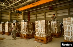 U.S. Army parachute riggers with the 11th Quartermaster Company, 264th Combat Sustainment Support Battalion, 82nd Sustainment Brigade, palletize meals for a humanitarian airdrop over Iraq at an undisclosed site in Southwest Asia, Aug. 7, 2014.