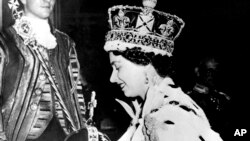 FILE - Britain's Queen Elizabeth II wearing the bejeweled Imperial Crown and carrying the Orb and Scepter with Cross, leaves Westminster Abbey, London, at the end of her coronation ceremony, June 2, 1953.