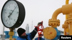 A worker turns a valve at the Nesvizhskaya gas compressor station some 130 km (81 miles) from Minsk, Jan. 9, 2009.