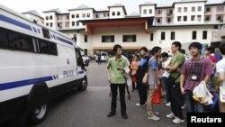 Sebuah van polisi Singapura siaga sementara para sopir bus asal Tiongkok melakukan aksi mogok di Singapura (26/11).