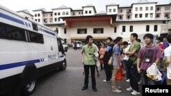 Một xe cảnh sát lùi ra khỏi khu nhà ở trong khi các cuộc đàm phán với các tài xế xe buýt vẫn tiếp tục diễn ra bên trong khu nhà, Singapore, 26/11/2012. (REUTERS/Edgar Su)