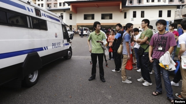 A police van leaves the premises of a dormitory as negotiations with striking bus drivers continue within the building in Singapore, November 26, 2012.