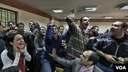 Para aktivis Mesir meneriakkan slogan-slogan anti dewan militer Mesir saat pengadilan atas aktivis HAM internasional di Kairo (26/2).