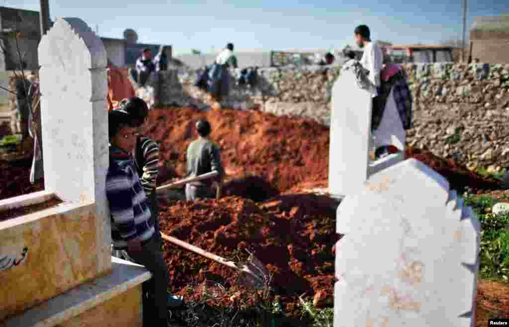 30일 시리아 아자즈 시의 묘지에서 무덤을 파고 있는 사람들과 지켜보는 아이들.