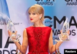"Taylor Swift poses with her CMA Pinnacle award as well as awards for Musical Event of the Year and for Music Video of the Year, both of the latter for ""Highway Don't Care,"" with Tim McGraw and Keith Urban, at the 47th Country Music Association Awards in N"