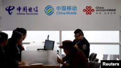 在上海舉行的中國國際進口博覽會上顯示的中國電信、中國移動和中國聯通的標識。(2018年11月5日)