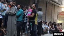 People line up for bread in the rebel-held al-Shaar neighborhood of Aleppo, Syria, July 14, 2016.